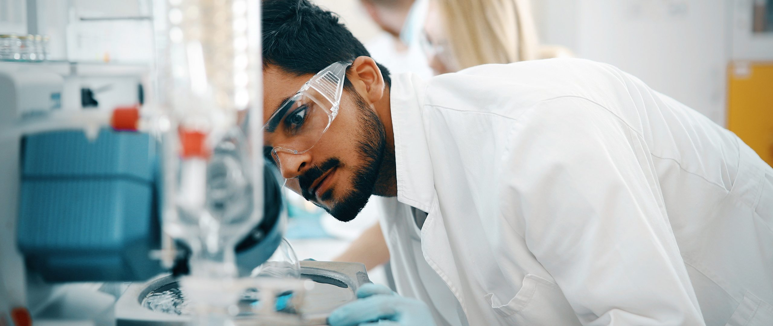 A technician in a lab coat leans in to examine a piece of laboratory equipment.