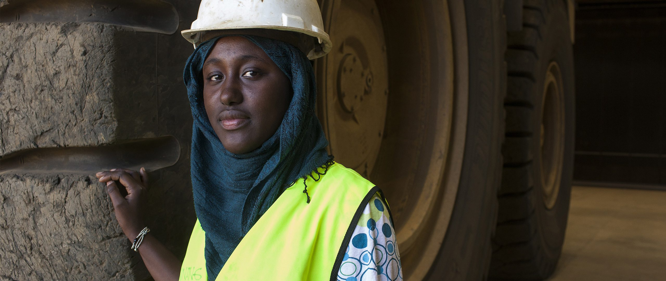 A woman in a headscarf and hard hat rests her hand on a tire so tall that it spills far out of the photograph.